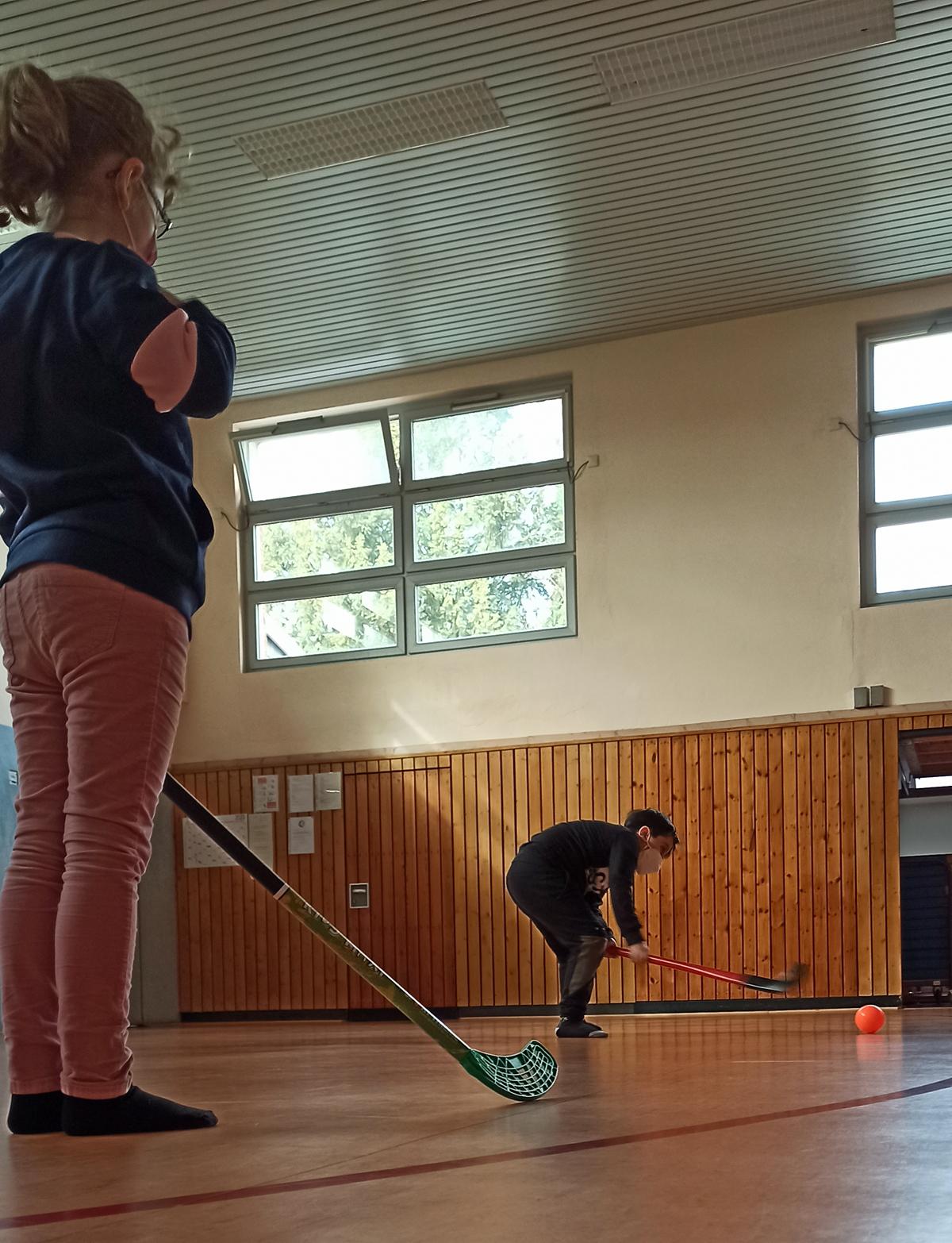 Kinder spielen Hockey in der Turnhalle
