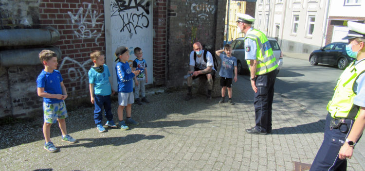 Kita-Kinder stehen an einer Hausmauer und werden von einem Verkehrspolizisten instruiert