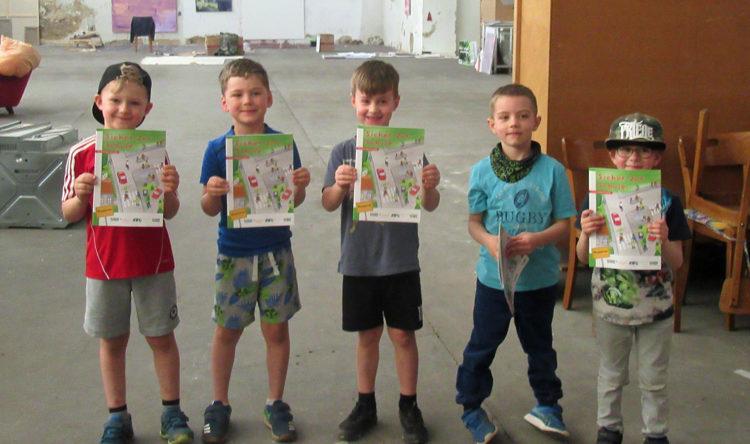 Fuenf Kita-Kinder zeigen ihre Ausmalhefte