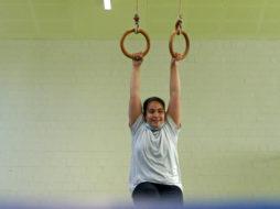Ein Mädchen macht Sport in der Halle an Ringen