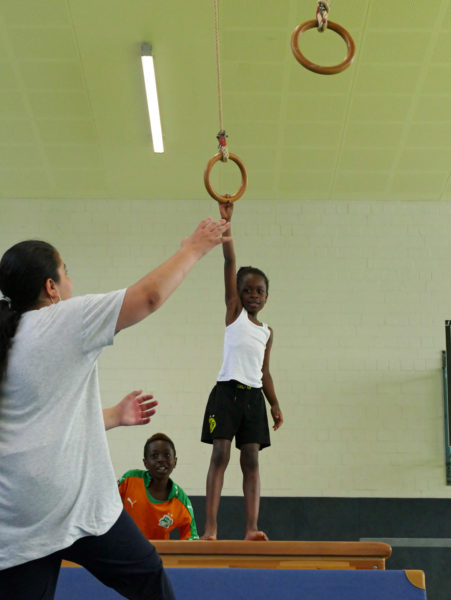 Kinder machen Sport in der Halle an Ringen